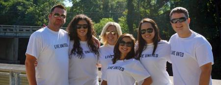 Six people wear Live United T-shirts