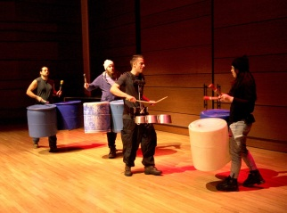 "Four cast members of ""STOMP"" perform on plastic buckets and pans."