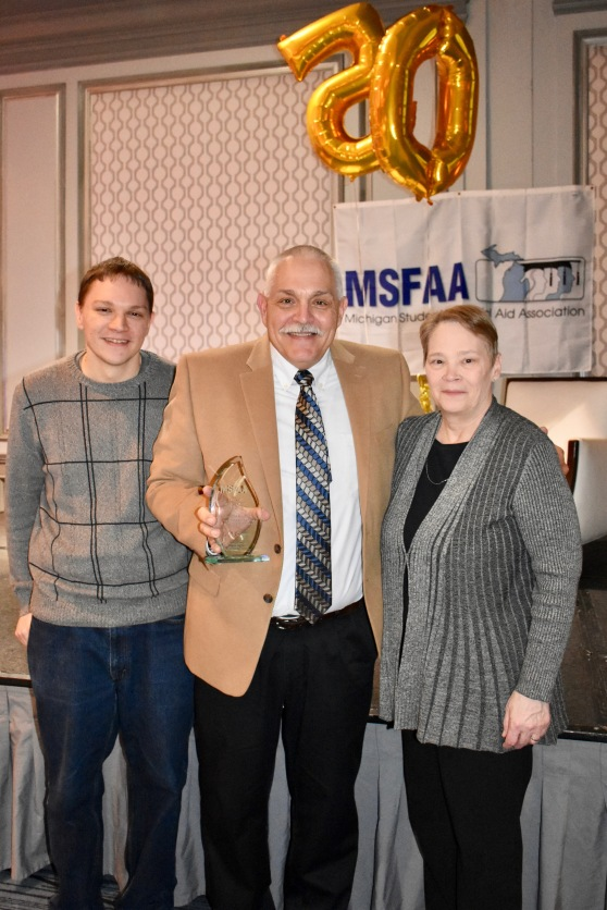 Paul Doane, holding an award, stands with his wife and his son Pete in front of the stage at the Michigan Student Financial Aid Association 50th anniversary celebration.