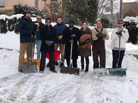 Eight members of the IT Department hold shovels as they stand on a freshly shoveled Fountain Street sidewalk.