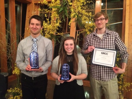 Sam Johnson, and Katie Schumann hold awards and Christopher Klap holds a certificate.