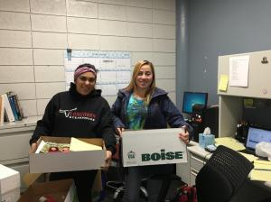 Two students hold up boxes of school supplies.