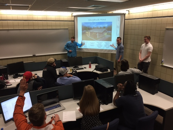 """Three students present their project to students seated in a classroom. They stand next to a video screen that says: """"Saugatuck Home."""""""