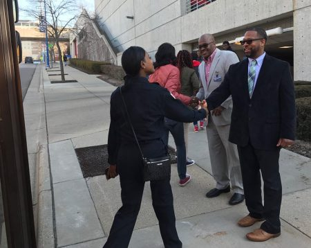David Selmon and Emmanuel Armstrong greet Ottawa Hills High School students as they get off a schoolbus.