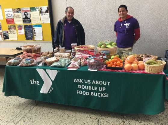 "Photo of two ""Veggie Van"" workers from the YMCA posing at a table full of produce in the Student Center"