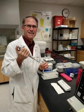 Bob Leunk in a lab classroom posing with equipment.