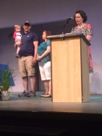 A woman stands on stage with a man holding a child while the presenter speaks at the podium.