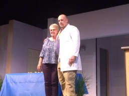 A woman and man pose on stage for a photo.