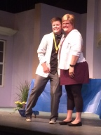 Two people pose on stage for a photo.