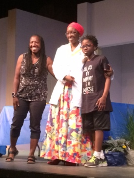 """Two women and one young adult wearing a """"Relax My Mommy is a Nurse"""" t-shirt pose for a photo on stage."""