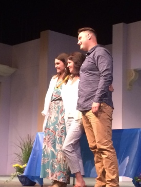 Two women and one man pose for a photo on stage.