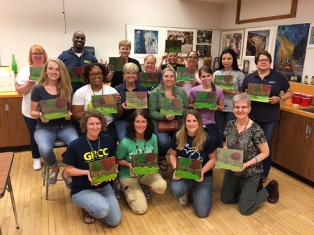 The School of Workforce Development APSS members show off their paintings after a group retreat.