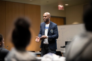 """A presenter talks during Raider Nation Day at GRCC. He is wearing a black blazer over a white t-shirt with text that reads """"Raider"""" in blue and """"Nation Day"""" below it in gold."""