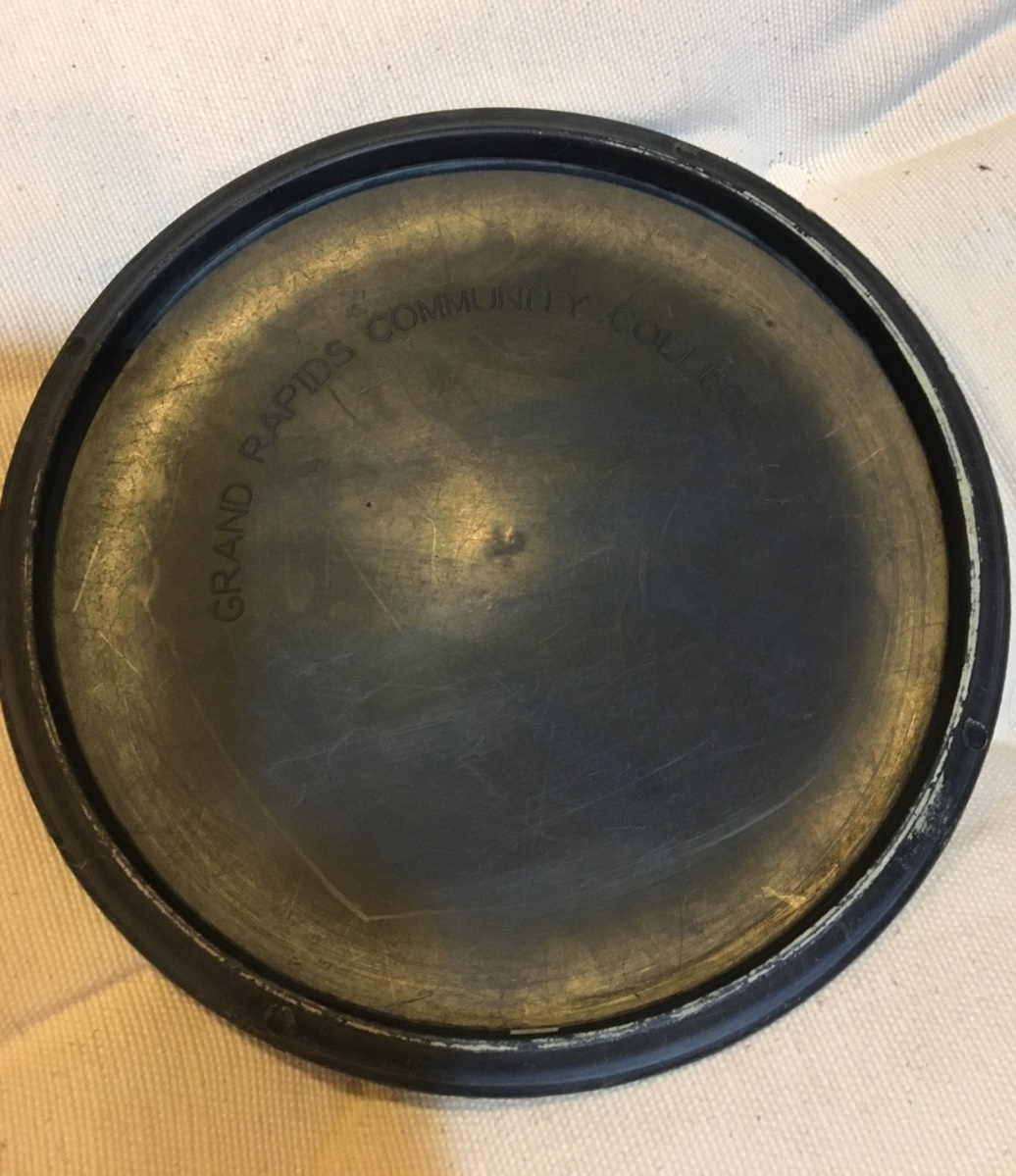 """A metal disc has """"Grand Rapids Community College"""" etched on it."""