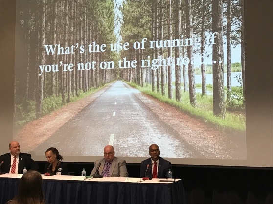 "President Bill Pink addressing the room during a panel-led discussion on the Marshall Plan at GRCC. The projected image behind the panelists shows a paved road through the woods with the words, ""What's the use of running if you're not on the right road..."""