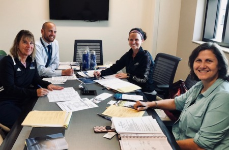 Four GRCC and GVSU staff members pose for a picture while sitting at a table and working on the new 2+2 transfer agreement.