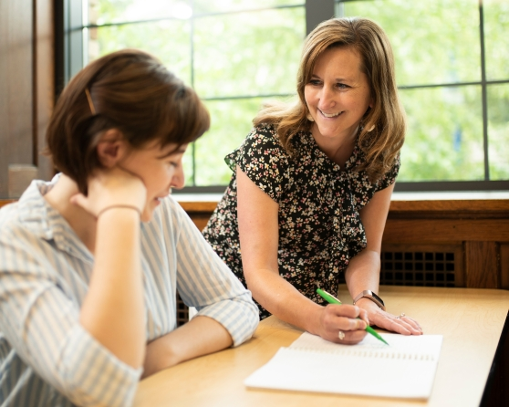 A photograph of a female instructor working with a female student in the Honors program.