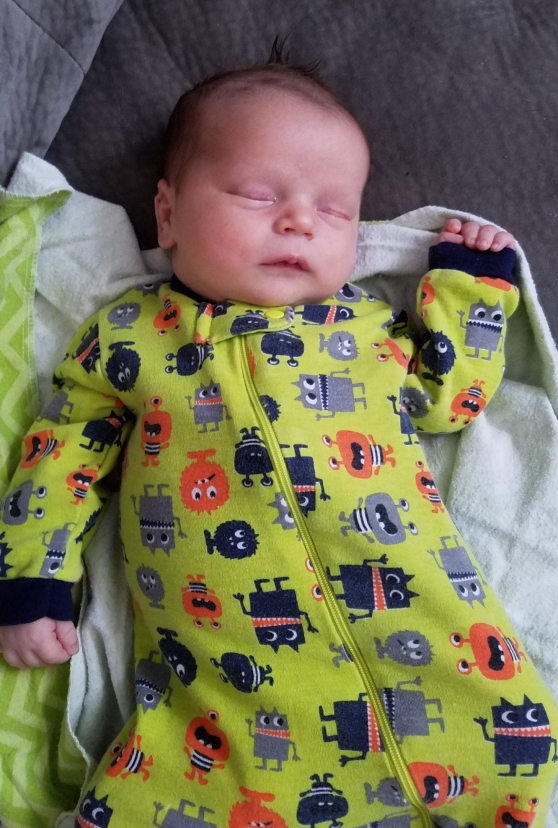 Photo of new baby Ryder Thomas Scott. The baby is sleeping and wearing a chartreuse onesie decorated with monsters,