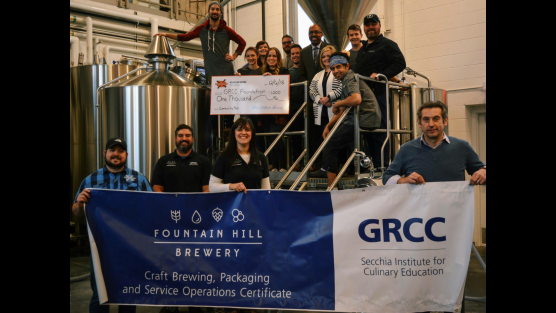 A photo of Dr. Pink and Fountain Hill Brewery members posing with a giant check written out to the GRCC Foundation.
