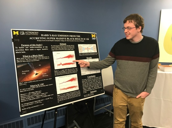 A student points to a posterboard describing his research project.