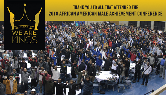 "A photo from the 2018 African American Male Achievement Conference. The photo shows the GRCC gymnasium packed full of attendees who are all standing and looking at the camera with right fists raised in the air. The text at the top reads: ""Thank you to all that attended the 2018 African American Male Achievement Conference."" At the top left is the logo for the AAMAC with the words ""We Are Kings"" underneath it."