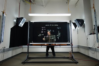 Lightboard example photo. A professor is shown demonstrating Lightboard usage in a studio.