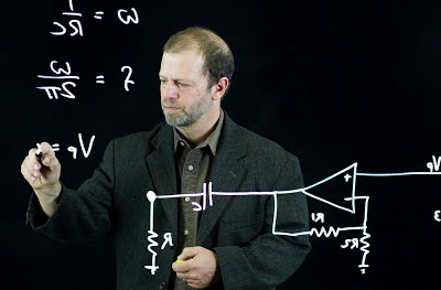 Lightboard example photo. The professor is shown as he would appear in the final recording, writing on what appears to be a glass wall.
