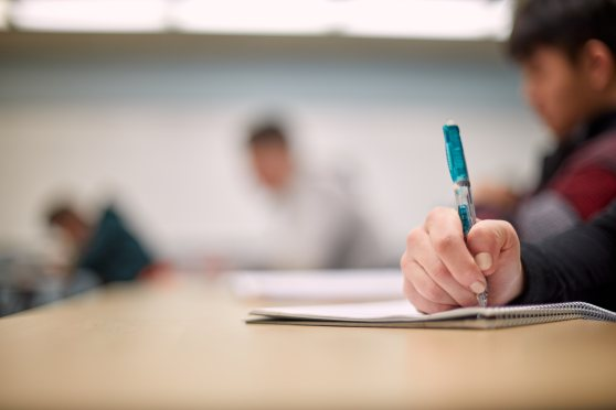 Image of GRCC Mathematics classroom. Focus is on a student's hand holding a mechanical pencil and writing in a notebook. Three other students are out of focus in the background.