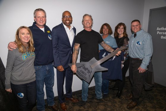 Dr. Pink, Julie Parks, and GRCC staff and families pose with Metallica guitarist James Hetfield has he hold the full-sized black metal guitar sculpture made by the GRCC Welding Dept.