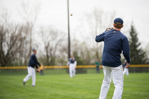 Photo of the Raiders baseball team at practice in the outfield.