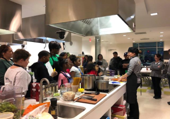 A group of young Culinary Medicine students working in the kitchen.