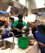 Young Culinary Medicine students pose for a photo while working in the kitchen.