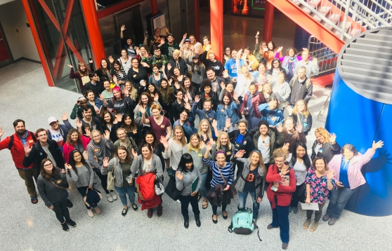 Group photo of the student, parent, staff, and faculty attendees of the 2019 Study Away Student Pre-Departure Orientation. Participants are gathered in the annex of the ATC, looking up and waving to the camera.