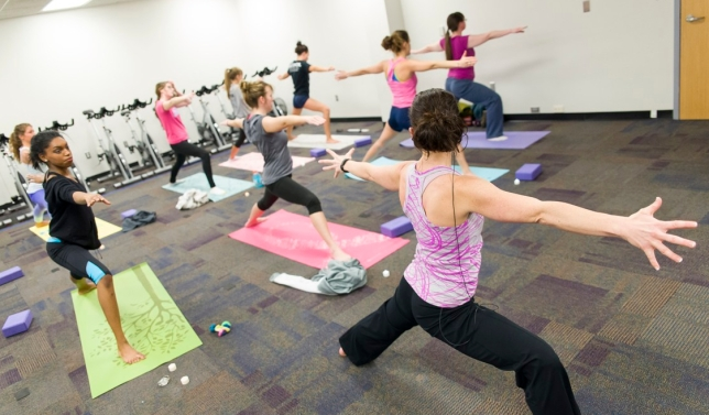 Photo of GRCC students in a Yoga class, mimicking the teacher in 'Virabhadrasana II' or the 'Warrior 2' pose