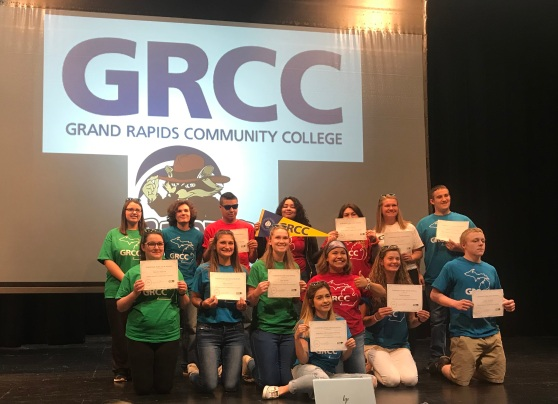 "Fourteen students on a stage hold up certificates. The video screen behind them says: ""GRCC. Grand Rapids Community College."""