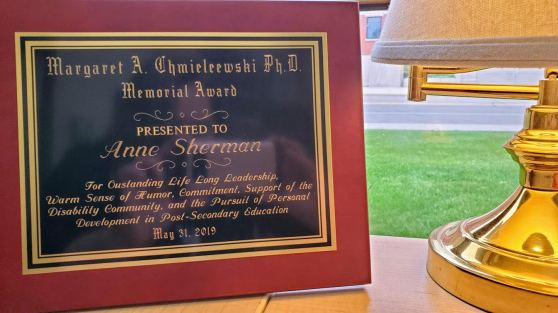 "The plaque for the Margaret A. Chmieleewski Ph.D. Memorial Award sits on a table. It says: ""Presented to Anne Sherman. For outstanding life long leadership, warm sense of humor, commitment, support of the Disability community, and the pursuit of personal development in post-secondary education. May 31, 2019."""