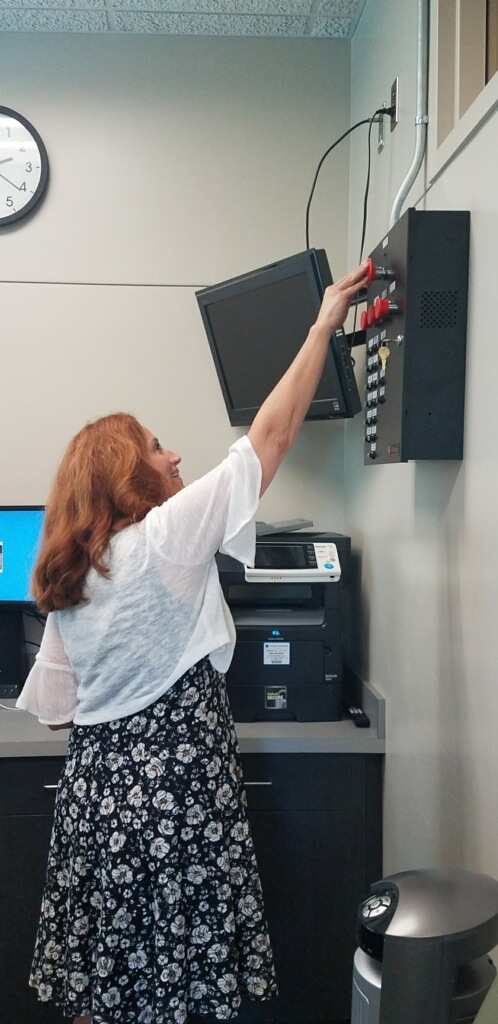 Lisa Freiburger reaches up to push the button to lockdown the campus.