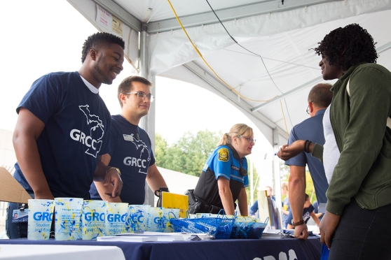 Two young men, wearing GRCC T-shirts and standing behind a table of giveaway plastic cups, talk to a student on the other side of the table.