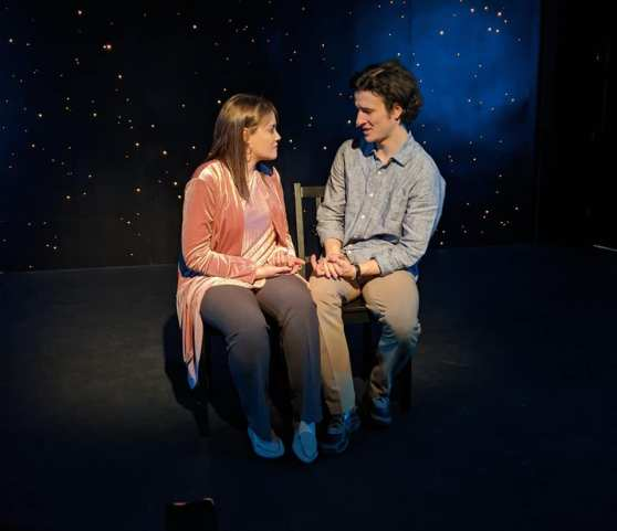 Yesenia Cotto and Anthony Snead sit on chairs on the Spectrum Theater stage.