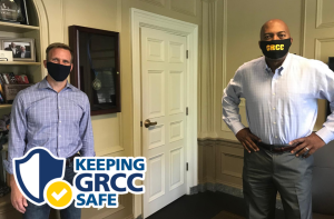 Brian Knetl and Bill Pink, both wearing face masks, stand in Pink's office.