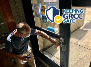 """Glenn Fox cleans a door: """"Keeping GRCC safe."""""""