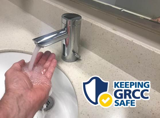 Someone uses a hands-free faucet in a men's room.