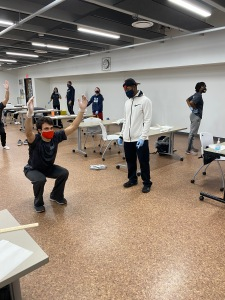 People learning stretching exercises while wearing PPE.