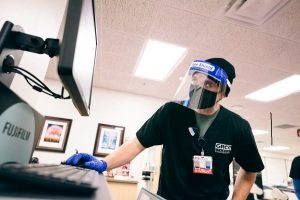 Student in mask and face shield looking at a computer.