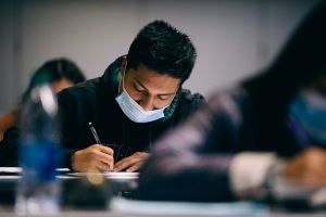 Student wearing a mask writing in a notebook.