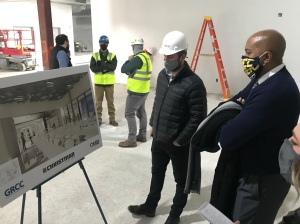 Picture of Bill Pink with construction workers looking at the final design of a new room in the JCPenney renovation project.