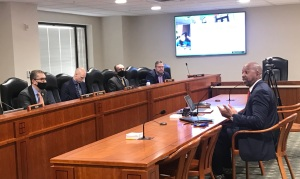 Pink sitting at a table, testifying before the state House of Representatives Appropriations Subcommittee on Higher Education and Community Colleges.