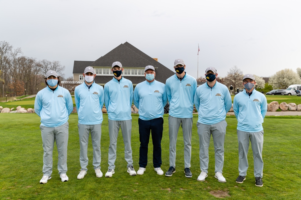 The six members of the golf team stand on either side of coach John Forton; all wear masks.