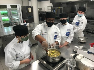 Two KCTC students and two GRCC students cooking in kitchen.