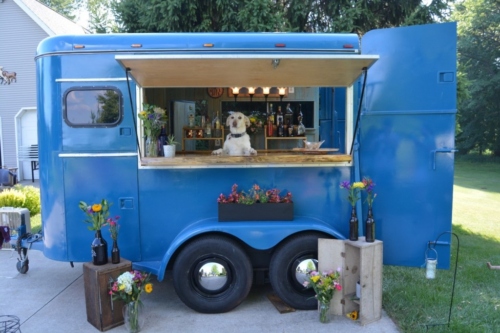 A dog stands on its hind legs behind a bar that has been built into a former horse trailer.
